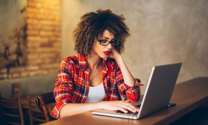 Black woman with curly hair, glasses, and red lipstick typing on her computer