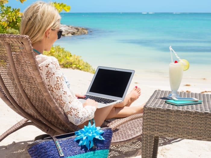 Blonde woman in a beach chair with a laptop on her lap, a cocktail beside her, and the ocean in view