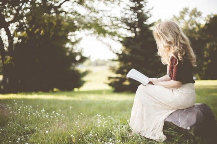 woman reading he bible in grassy field - article about monetizing a christian blog
