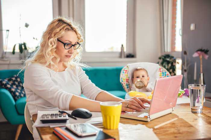 Mother with baby using laptop at home office