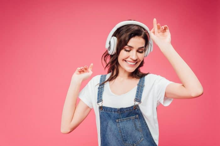 Brunette woman with headphones on, dancing and smiling.
