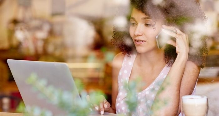 Beautiful black woman with curly hair, sitting in front of her laptop and talking on the phone