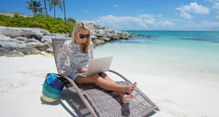 blonde woman in a beach chair with a laptop on her lap and ocean in the background